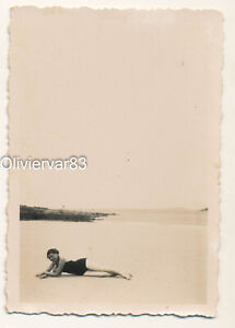 Vintage photo 1937 - pretty woman in swimsuit laying on empty beach