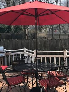 Patio dining set and chaise lounge with cushions and umbrella