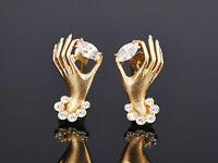 Süße Ohrstecker – elegante Hände halten einen weißen funkelnden Stein – Gold 750