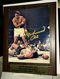 MUHAMMAD ALI AUTOGRAPHED 8x10 COLOR PHOTO-OVER LISTON--STACKS of PLAQUES DISPLAY