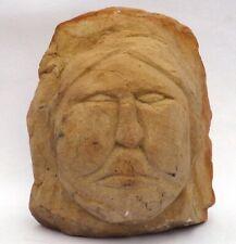 A strong, primitive face carved from sandstone. Folk art, outsider art sculpture
