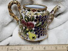 White ceramic teapot with colorful mosaics of fruits and flowers