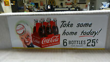"""COCA COLA W/ 6 PACK BOTTLES"" METAL EMBOSSED ADVERTISING SIGN. MEASURES 28"" x 10"