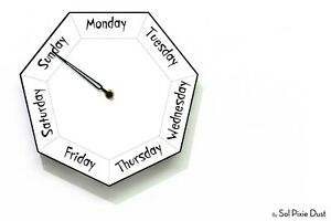 DayClocks - Hexagon White Wall Clock - Day of The Week Clock - Fun Clock Gift