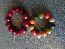 Two wooden beads bracelets - one deep auburn red, the other greenish colours
