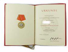 #e7000 DDR atto medaglia al merito della NVA in oro conferito 1976