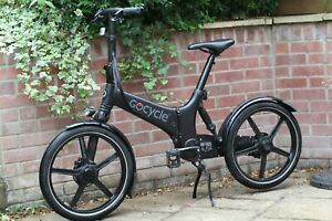 Black GoCycle GX fast-folding electric bike with box, lights, and mudguards