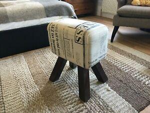 Designer fabric-covered stool, newspaper-print design, wooden legs