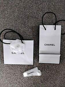 Two x White CHANEL Gift Bags, including flower and ribbon. Rope handles. Empty.