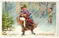 101620 LOVELY VINTAGE CHRISTMAS POSTCARD SHOPPER IN COLD, WIND AND SNOW EMBOSSED