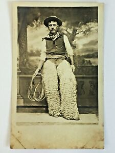 RPPC Cowboy Wearing Wooly Chaps & Holstered Pistol Holding Lasso