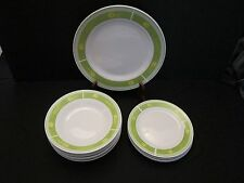 White dishes with a green trim and  Yellow flowers
