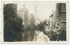 Unidentified location, medieval buildings by river, distinctive church spire