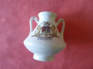 A PIECE OF  CRESTED CHINA IN THE FORM OF A 2 HANDLED POT -- BRISTOL