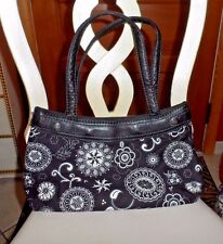 Thirty One Black handbag wearing a black and white skirt