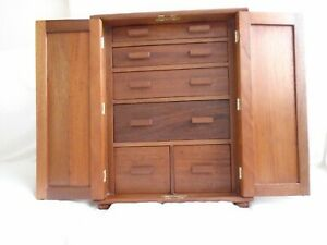 A six drawer storage cabinet with doors in mahogany