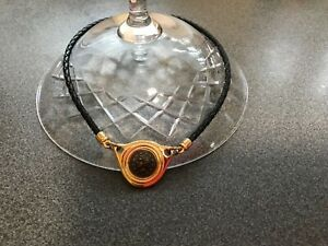 Coin pendant set in gold plated surround with black plaited leather