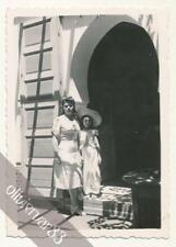 Woman and daughter in nice dress on door step - vintage photo