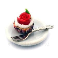 Miniatura Rojo Rosa Magdalena en una taza de papel Violeta en una placa con un tenedor