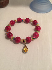 Stretch bracelet made with red beads and gold spacer beads and a yellow charm
