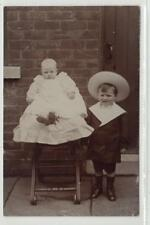 Picture postcard of a boy in a sailor suit and a baby in a high chair (C34184)