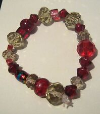 Lovely elasticated beaded bracelet with great variety of red and smokey beads