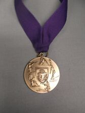 silver female Softball medal with purple neck drape trophy