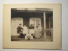 2 Männer & 2 Frauen & Junge sitzen vor einem Haus auf der Veranda / KAB