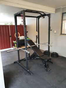 Home gym, barbell, bench, weights, cage and floor.