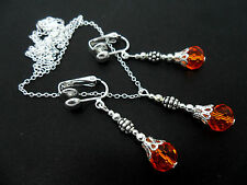 A SILVER PLATED ORANGE CRYSTAL  NECKLACE AND  CLIP ON EARRING SET. NEW.
