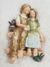 Young Couple Holding Hands Sitting on a Bench Figurine