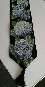 Black woven wall hanging decorated with blue and purple hydrangeas black tassel