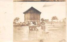 Eddyville Iowa~Farm Children~Baby Girl in High Chair~Boy in Wagon~Barn~1915 RPPC