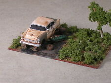 HO 1955 Rusted Out Chevy up on blocks with man on creeper diorama.