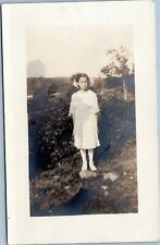 postcard rppc Girl in white with bows in hair standing outside 1918-1930 AZO