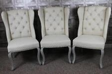 BUTTON BACK WINGED FRENCH STYLE DINING CHAIRS IN CREAM LINEN WITH LIMED LEGS