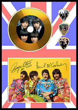 The Beatles A4 gold disc and guitar picks on photo display