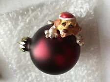 Wrinkled Gold Santa Dog on top of the Red Round Glass Ornament