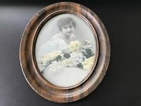 Vintage portrait of a lady with flowers, placed in a oval metal frame