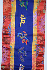 Embroidered Tibetan OM on blue silk from Nepal with red and yellow silk border