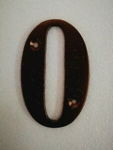Black metal door number 0.