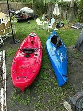 Wilderness systems and old Town kayaks,with paddles and wheeled tote.
