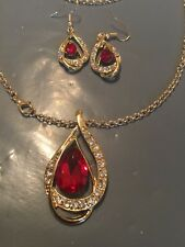 gold earrings and necklace set with red stone surrounded wite c z stones