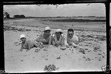 Négatif photo ancien - Portrait de famille, allongé dans le sable plage - mer
