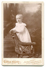 YOUNG CHILD STANDING, WICKER CHAIR. SCRANTON, PA.