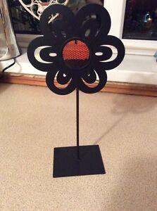 A BLACK METAL FLOWER TEA LIGHT HOLDER WITH A ORANGE CENTRE