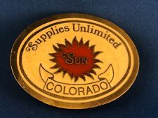 "Supplies Unlimited ""SUN"" Colorado oval brass belt buckle, off-white, red inlays"