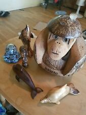 Hawaiian figurines carved out of mahogany wood, a coconut and a snow globe.