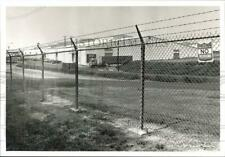 New listing 1988 Press Photo Chain Link Fence and Ore Piles at Navy Depot on Brandy Lane