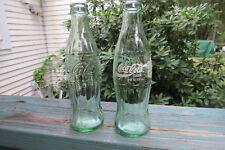 2 green glass Coca Cola,Coke bottles,hobbleskirt,1 applied white color,1 clear
